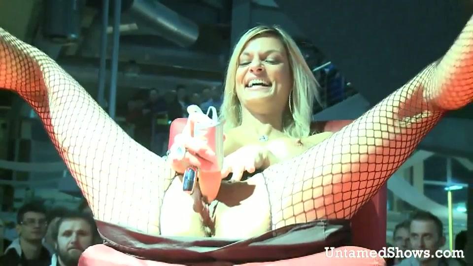 Dildo test door blonde hoer op het podium.