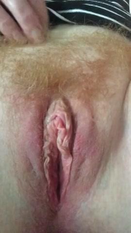 Voor de webcam masturbeert de geile huisvrouw haar behaarde kut